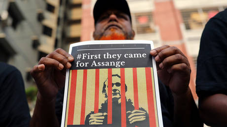 A man holds a sign supporting WikiLeaks founder Julian Assange. FILE PHOTO: © Reuters / Mohammad Ponir Hossain