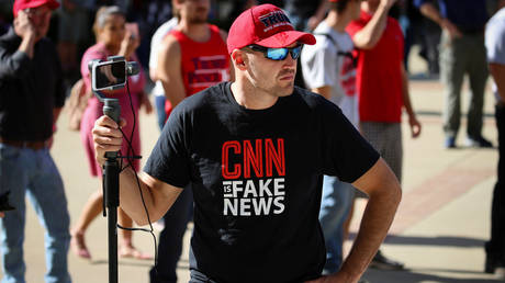 "A supporter of President Donald Trump wears a ""CNN is fake news"" t-shirt"