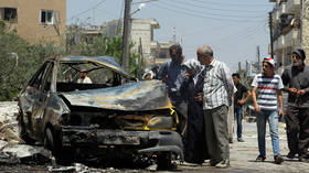 Civilians inspect a burnt car at a site hit by an airstrike in the rebel-controlled city of Idlib, Syria June 29, 2016. © REUTERS/Ammar Abdullah