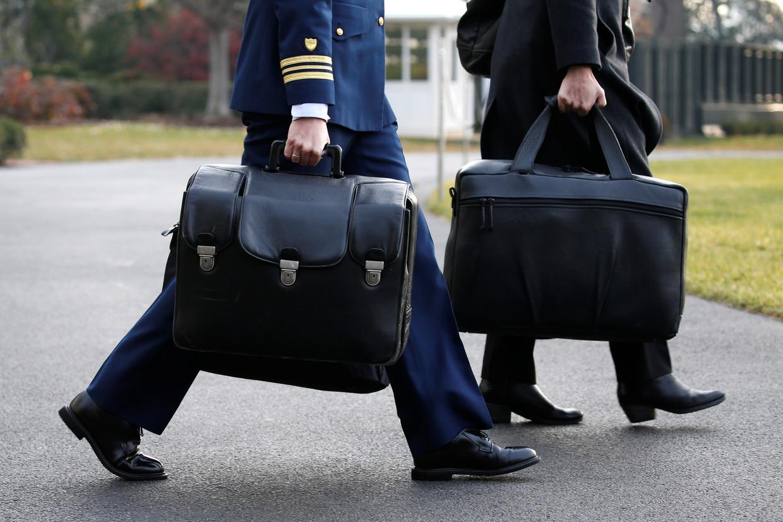 """Um assessor de Trump carrega a chamada """"a bola de futebol nuclear"""", que contém códigos de lançamento para o arsenal nuclear dos EUA e que viaja com o presidente dos EUA sentado, 4 de dezembro de 2017 © Reuters / Jonathan Ernst"""