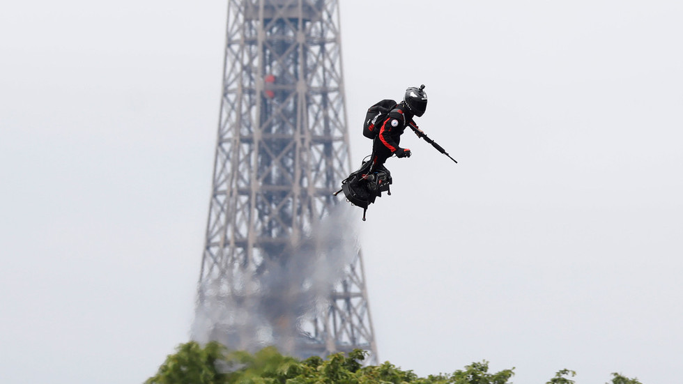 'The Green Goblin!': Onlookers delighted as armed flyboard rider soars over Paris
