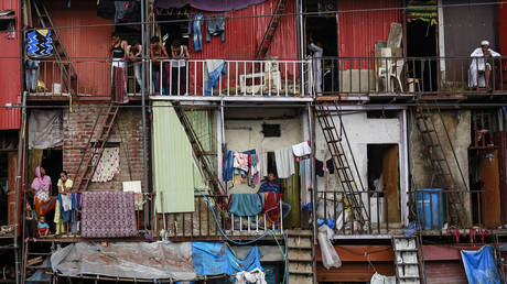 Residents stand in their shanties at a slum in northern suburb of Mumbai, India © Reuters / Danish Siddiqui