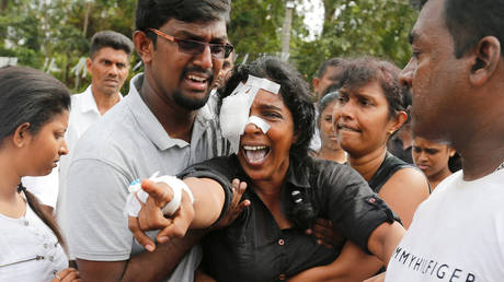 Kumari Fernando, who lost her husband and two children during the bombing at St Sebastian's Church yells towards the graves during a mass burial for victims of Colombo bombings. File photo.