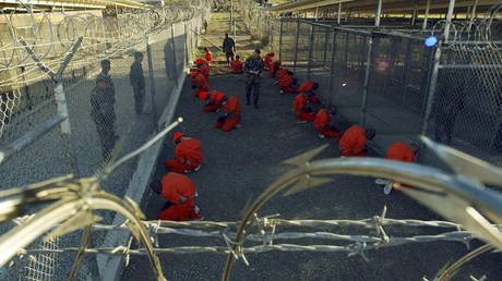 File photo of detainees sitting in a holding area at Naval Base Guantanamo Bay, Cuba В© Reuters