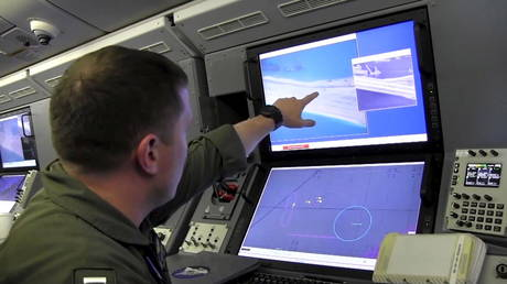 A US Navy crewman aboard a P-8A Poseidon surveillance aircraft