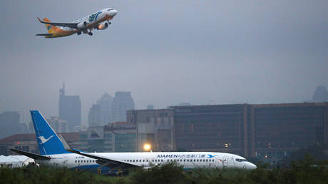 A Cebu Pacific Airbus A320-200 passenger aircraft takes off above a Xiamen Airlines Boeing 737-800 in Paranaque, Metro Manila in Philippines, August 17, 2018.