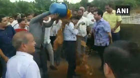 Indian politician & supporters drench engineer with mud in road protest (VIDEO)