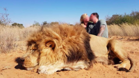 'Sick' hunting couple slammed for smooching over corpse of dead lion