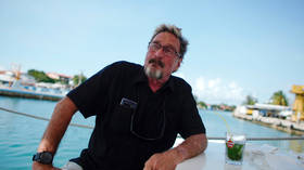 McAfee claims CIA tried to 'collect' him, poses armed in boat with his wife (PHOTO)