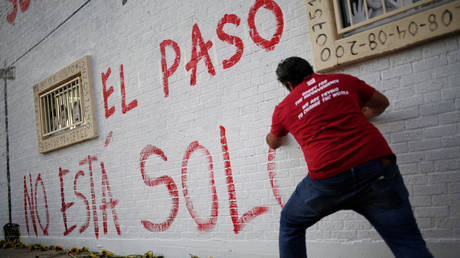 """A man takes part in a rally against hate a day after a mass shooting at a Walmart store, in El Paso, Texas, U.S. August 4, 2019. Graffiti reads """"El Paso Is Not Alone"""" © REUTERS/Jose Luis Gonzalez"""