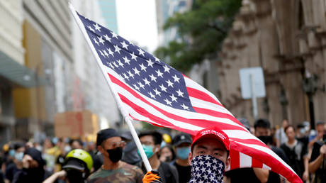 A protester carries a US flag during the march at Mongkok, in Hong Kong, China, August 3, 2019.