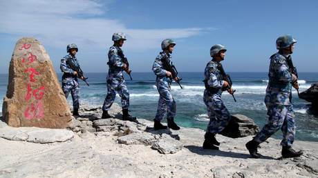 Soldiers of Chinese People's Liberation Army Navy (PLAN) patrol an island in the South China Sea (file photo)