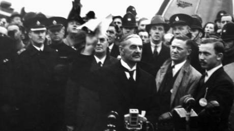 Prime Minister of the UK Arthur Neville Chamberlain waves the Munich Agreement (1938), which conceded the Sudetenland region of Czechoslovakia to Nazi Germany.