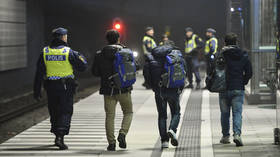 FILE PHOTO A police officer escorts migrants from a train at Hyllie station outside Malmo, Sweden. ©  Reuters / Johan Nilsson