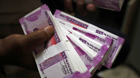 A cashier displays the new 2000 Indian rupee banknotes inside a bank in Jammu. File photo