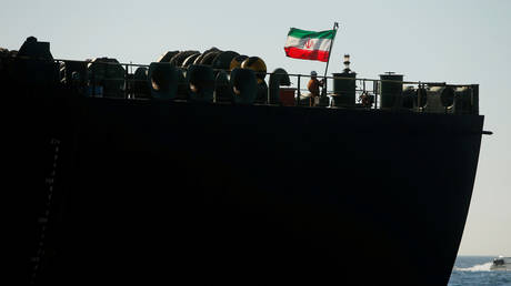 A crew member raises the Iranian flag on Iranian oil tanker Adrian Darya 1, previously named Grace 1, in the Strait of Gibraltar, Spain. File photo.