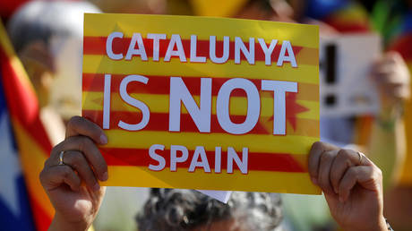 """A protester holds a poster with the slogan """"Catalunya is not Spain"""" during a demonstration to ask for the Parliament inclusion of the 3 Catalan elected MEP's Puigdemont, Oriol Junqueras and Toni Comin, in front of the European Parliament in Strasbourg, France, July 2, 2019. © REUTERS/Vincent Kessler"""