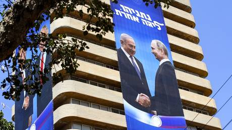 "Election banner of Israeli Likud Party, showing Benjamin Netanyahu shaking hands with Vladimir Putin, with a caption in Hebrew: ""Netanyahu, in another league."" © AFP / Jack Guez"