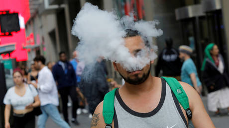 FILE PHOTO: A man uses a vape as he walks on Broadway in New York City © Reuters / Andrew Kelly