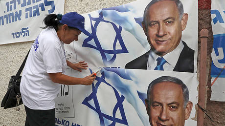 A woman places electoral banners for the Likud party showing chairman and Israeli Prime Minister Benjamin Netanyahu in the southern Israeli city of Beersheva on September 15, 2019.