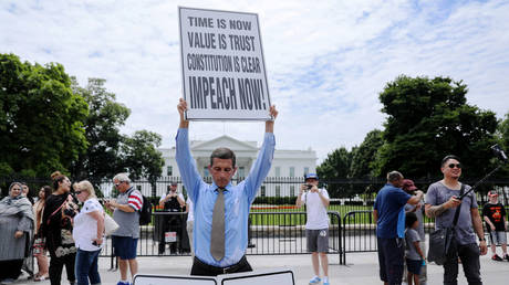 """Steve Swanson protests in silence with a sign over his head reading """"Impeach Now!"""" in front of the White House in Washington, U.S. June 19, 2019.  © REUTERS/Jonathan Ernst"""