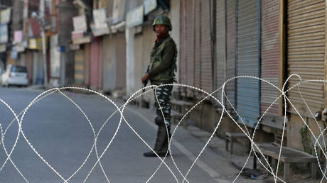 FILE PHOTO An Indian security force personnel stands guard in front of the closed shops during restrictions following scrapping of the special constitutional status for Kashmir by the Indian government, in Srinagar, September 10, 2019.