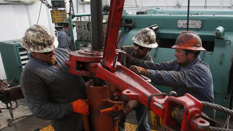 Roughnecks wrestle pipe on a True Company oil drilling rig outside Watford, North Dakota, US