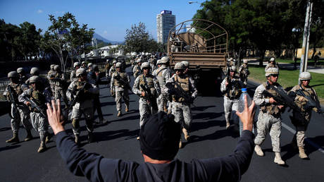 A demonstrator gestures as Chilean soldiers advance carrying their weapons, during a protest in Santiago, Chile, October 20, 2019
