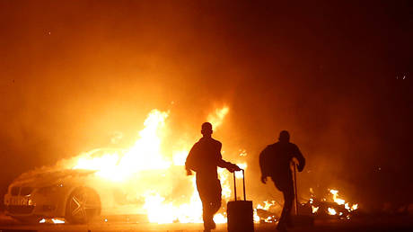 People run while a vehicle burns during riots at Hal Far Open Centre migrant camp in Hal Far, Malta, October 21, 2019