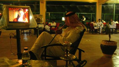 A Saudi citizen smokes a hookah (traditional waterpipe) while watching TV at a cafe in Riyadh