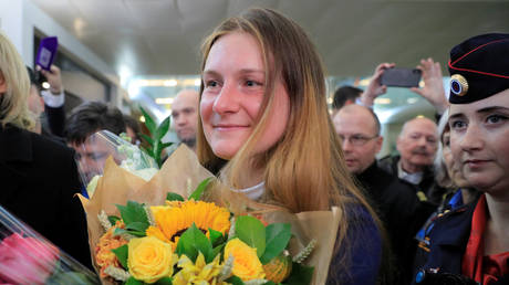 Maria Butina, who was released from a Florida prison and then deported by U.S. immigration officials, holds flowers upon her arrival at Sheremetyevo International Airport outside Moscow, Russia October 26, 2019. © REUTERS/Tatyana Makeyeva