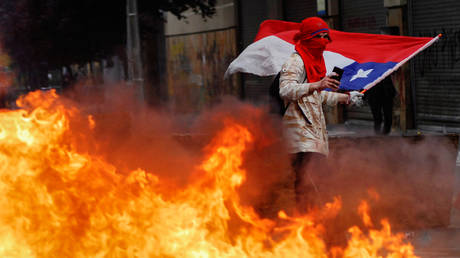 A protester walks past a burning barricade in Concepcion, Chile © Reuters / Jose Luis Saavedra