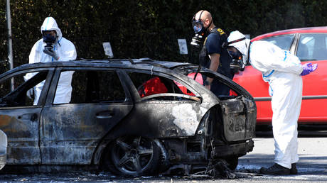 Police and criminal technical investigators look at a burnt car near the area of a shooting in Ribersborg, August 2019 © Reuters / Johan NIlsson