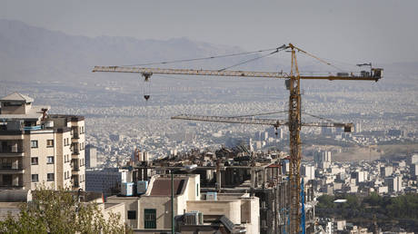 FILE PHOTO: Construction cranes work on a high rise buildings in Tehran.