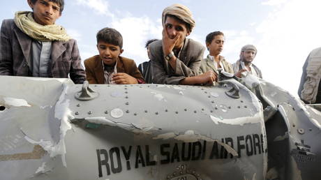 FILE PHOTO. People in Yemen stand by part of a downed Saudi fighter jet. ©REUTERS / Khaled Abdullah