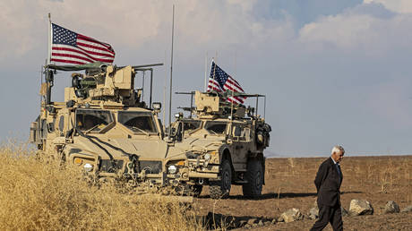 A Syrian man walks on as US armoured vehicles patrol the northeastern town of Qahtaniyah at the border with Turkey, on October 31, 2019.