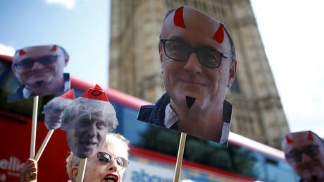 FILE PHOTO: Anti-Brexit protesters hold signs featuring Dominic Cummings in London © Reuters / Henry Nicholls