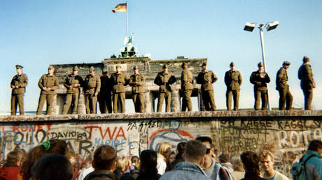 East German border guards stand on a section of the Berlin Wall on November 11, 1989. © Gunther Kern / AFP