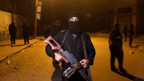 A Palestinian Islamic Jihad militant stands guard at the scene of an Israeli strike that killed the group's field commander Baha Abu Al-Atta in Gaza City November 12, 2019. © REUTERS/Mohammed Salem