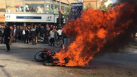Iranian protesters gather around a burning motorcycle during a demonstration against an increase in gasoline prices. ©AFP