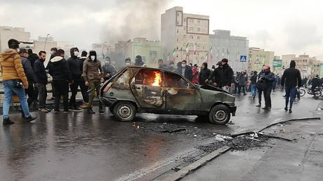 Iranian protesters gather around a burning car during a demonstration against an increase in gasoline prices in the capital Tehran, on November 16, 2019 © AFP