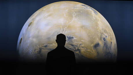 A person is seen against a projection of the planet Mars.