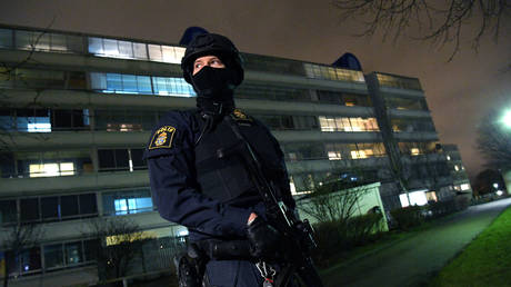 A policeman looks on after an object exploded next to a police station in Rosengard, Malmo