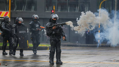 A riot police officer uses a tear gas weapon during a protest in Bogota, Colombia, November 21, 2019.
