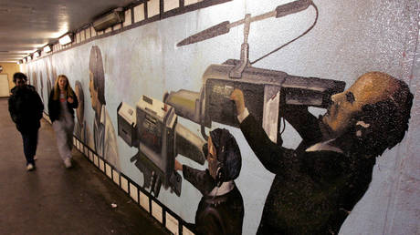 Pedestrians pass a mural showing camera operators in an underpass beside the BBC's main offices