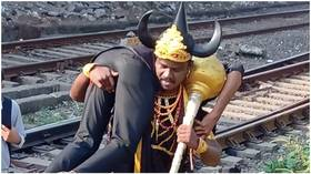Railway officials summon horned GOD OF DEATH to drag people off railway tracks in India (VIDEOS)