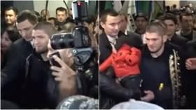 Trumpets, babies & cavalcades: Watch Khabib get mobbed as he arrives in Uzbekistan ahead of cousin's fight