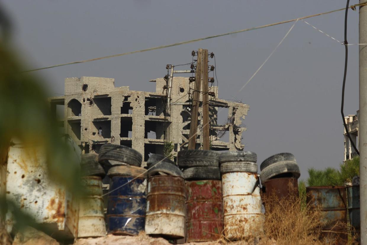 An Al-Nusra Front military building looms above the metal barrels that protect civilian neighborhoods from sniper fire. Al Zahraa, west Aleppo. ©  Vanessa Beeley