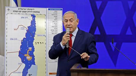 Benjamin Netanyahu speaks before a map of the Jordan Valley, which he wants to annex. © AFP / Menahem Kahana