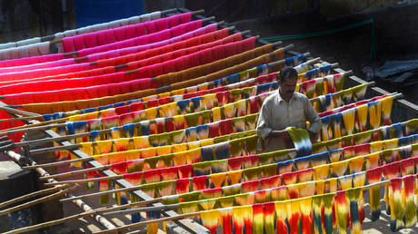A Pakistani worker dries fabric threads after dyeing them at a factory in Lahore on February 11, 2019. ©  AFP / Arif Ali